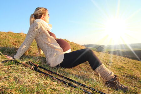 pregnancy exercise: Pregnant woman rest in sunset