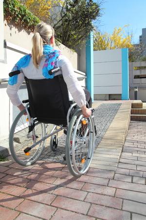 paraplegico: Mujer en una silla de ruedas en una rampa para sillas de ruedas
