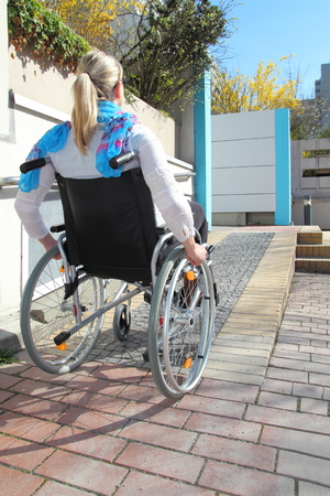 disable: Woman in a wheelchair on a wheelchair ramp Stock Photo