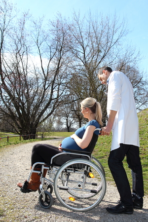paraplegic: Pregnant woman in wheelchair with doctor Stock Photo