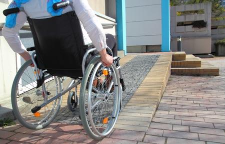 escalera: Mujer en una silla de ruedas con una rampa Foto de archivo