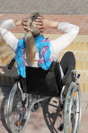 wheelchair access: A young female Wheelchair user in front of a stair
