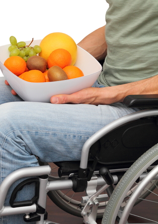 paraplegia: A male healthy Wheelchair user with a fruit bowl