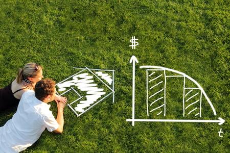 equidad: Una pareja en una pradera de cepillado de pr�stamos de hipoteca para una casa Foto de archivo