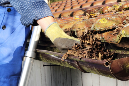 gutter: Man Cleaning a rain gutter in Close up Stock Photo