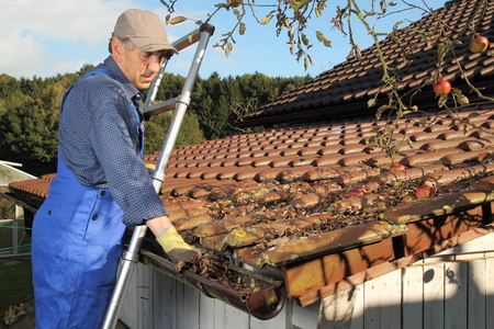 Ein Mann Reinigung einer regen Dachrinne auf einer Leiter Standard-Bild - 32280215