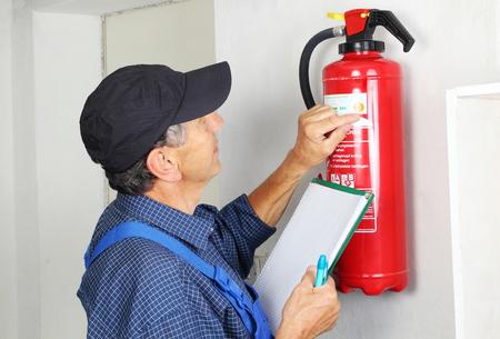 mantenimiento: Una comprobación Profesional extintor incendiada