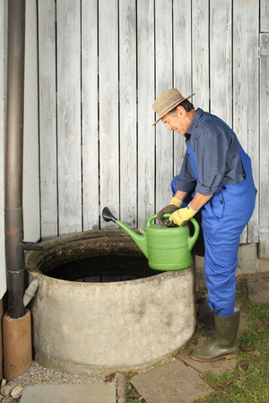 diving save: A Gardener next to his Rain water barrel Stock Photo