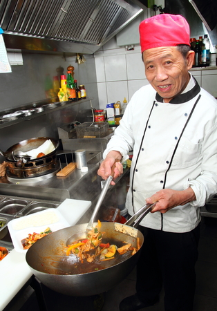 A Asia cook with wok take away Standard-Bild