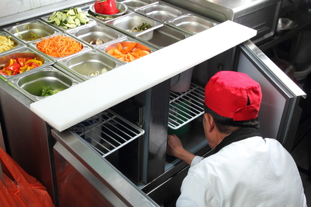 asian chef: A Asian cook in a citchen working on a vegetable buffet bar