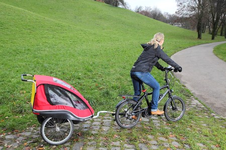 A Mother riding a E-Bike with child trailer photo