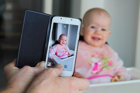 9 months: Taking a picture of a eating baby with a mobile phone Stock Photo