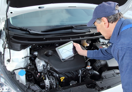 engine compartment: A car Mechanic with diagnostic equipment tablet