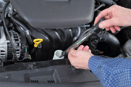 antifreeze: Man Checking Antifreeze in a Car collant System Stock Photo