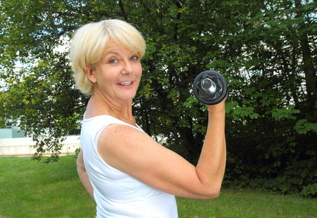 50 to 60: A Elderly woman doing outdoor training in a park with dumbbell