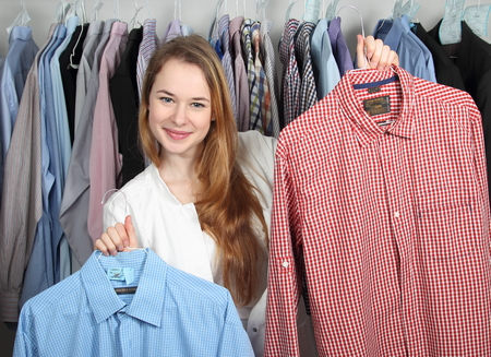 A Employee of a dry cleaning presenting two clean shirts Archivio Fotografico