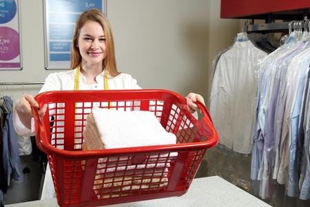 lavar: Un empleado de una limpieza en seco con un cesto de la ropa