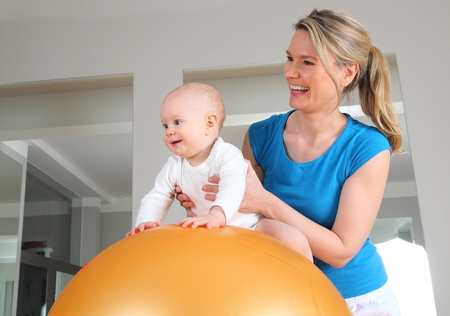 physiotherapist: A Physiotherapy with Baby on a Fitness Ball Stock Photo