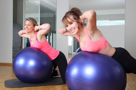 musculoskeletal: Two women in a fitness center together on a Fitness Ball