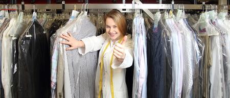 clothes washing: Una mujer en la limpieza en seco betwee camisas con el pulgar arriba