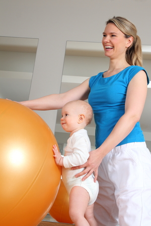 A Baby standing at Physiotherapy beside a Fitness Ball