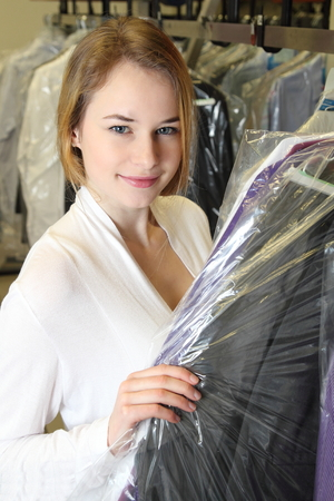 A Woman picks up clothes in a  Dry Cleaning