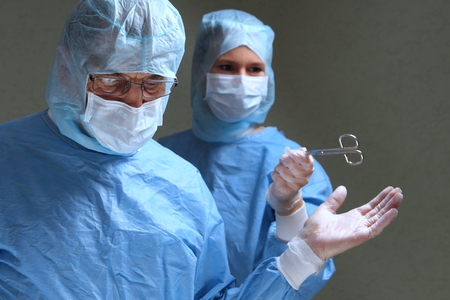 gives: A Assistang gives doctor scissors in a op Stock Photo