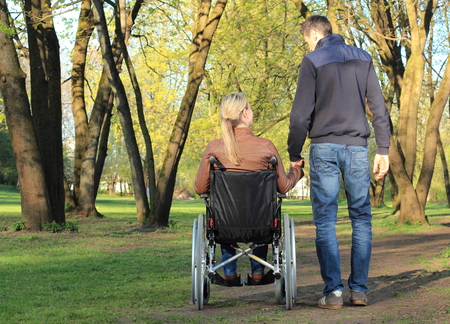 A Lovers couple in wheelchair and not handicapped Stock Photo