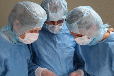 practical: Three doctors working concentrated in a OP room