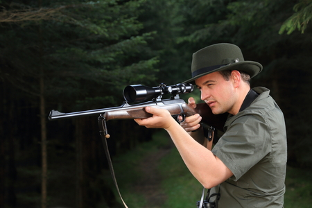 hunter man: A Hunter shooting with his rifle