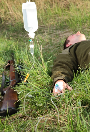 hunting rifle: A Hunter wiht infusion after a Hunting accident Stock Photo