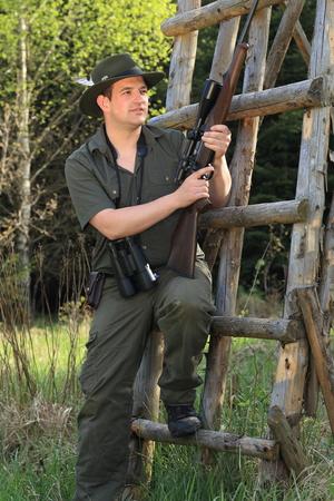 gunshot: A Hunter leaning on a tree stand