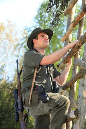 A Hunter climbing with hearing protection a high seat