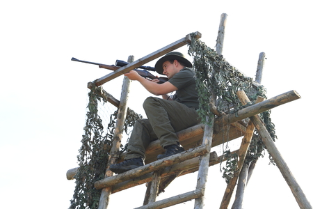 A Hunter with rifle shooting on a high seat
