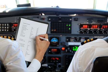 pilot cockpit: Two Pilots in aircraft with a checklist Stock Photo