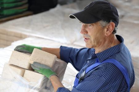 holzbriketts: Ein Mann mit Holzbriketts in einem storeage