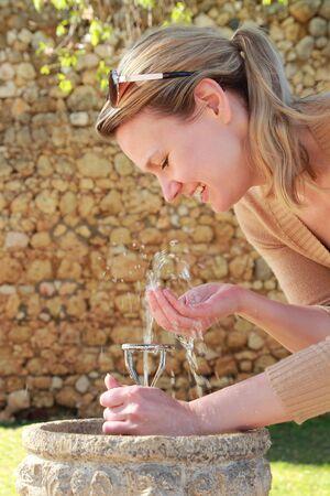 fountain: A Woman drinking water on a public fountain bubbler