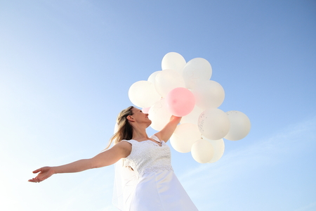 formalities: A Happy Bride with white ballons in blue sky Stock Photo