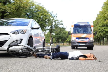 working accident: A Young Woman with bicycle accident and comming ambulance car