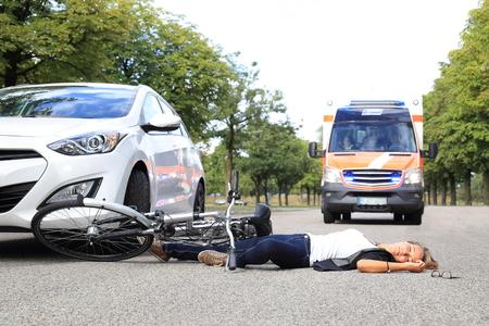 accidente trabajo: Una mujer joven con el accidente de bicicleta y comming coche de la ambulancia Foto de archivo