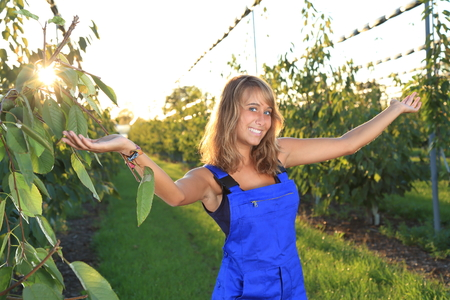 tree fruit: A Female gardener with outstreched armes in a greenhouse