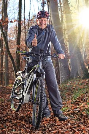 fall landscape: A Senior with e-bike MTB and thumb up