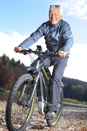A Senior on e-mountain bike beside a river