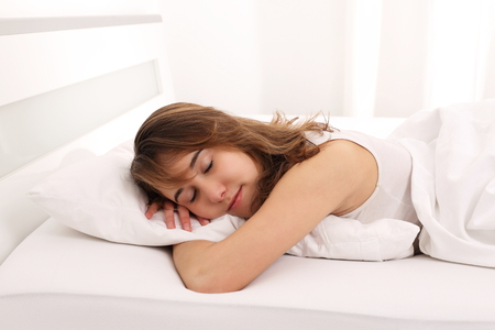 A Young Woman sleeping in bed with arm unter pillow