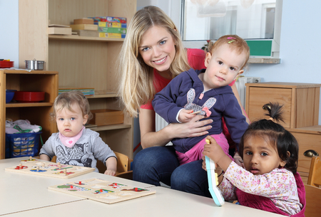 A Day care or kindergarten kids and teacher playing with a puzzle Stockfoto
