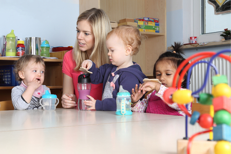 Some Kindergarten or nursery kids at a table drinking and playing with the teacher Reklamní fotografie - 55742664