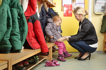 Mother picking up her child from a Kindergarten in wardrobe Stockfoto
