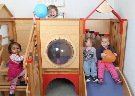 babies playing: A International Kindergarten with four kids playing on a slide Stock Photo