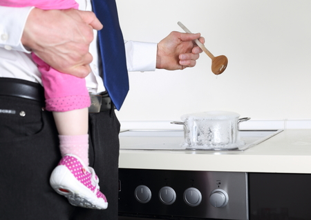 dad and daughter: A Businessman cooking with Baby on arm Stock Photo