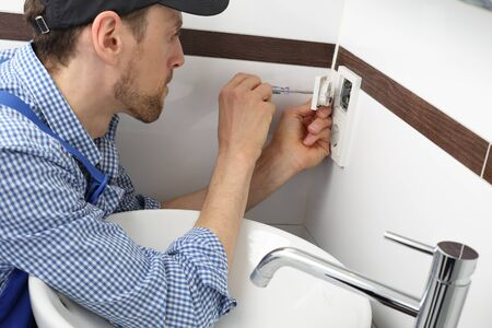 A Electrician changing a socket outlet in bathroom Stock Photo
